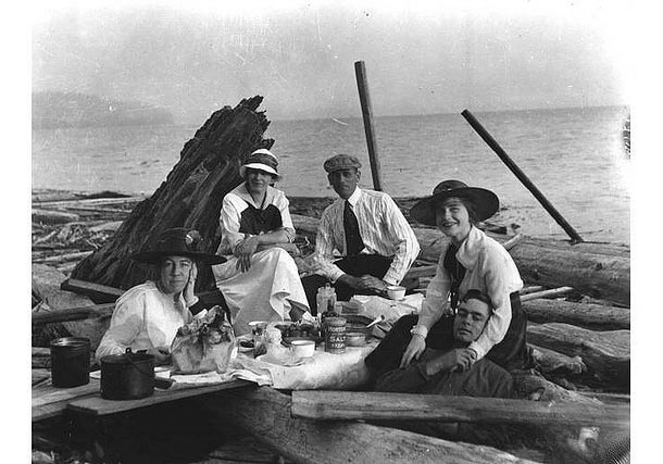 A picnic amidst driftwood at a beach near Seattle, WA, c. 1915.