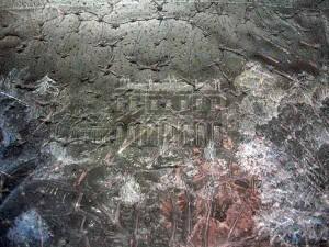Light through the heat damaged, large format negative reveals the image