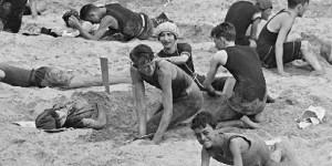 Candid 1900 beach scene, boys bury a girl